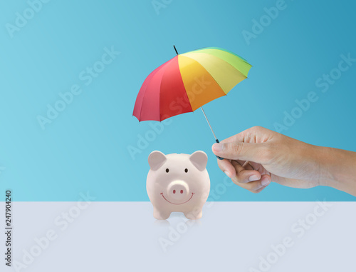 pink piggy ceramic bank with colorful rainbow umbrella, safe insurance - 247904240