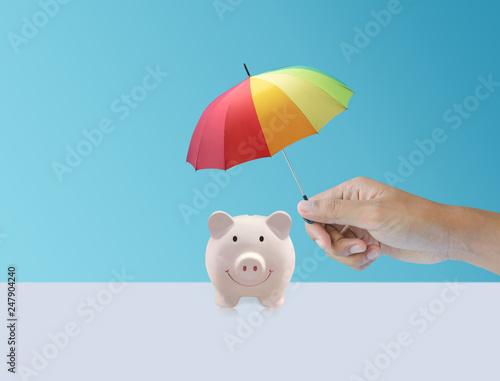 Leinwanddruck Bild pink piggy ceramic bank with colorful rainbow umbrella, safe insurance