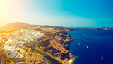 View of the Santorini Island with a smooth sea blue surface and steep shores with light struck place on the left