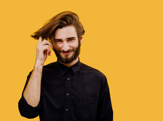 beautiful man with modern hairstyle, smiling emotionally in the frame, isolated on yellow background, © Alexandr