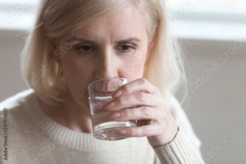 Leinwandbild Motiv Close up portrait aged woman drinking still water