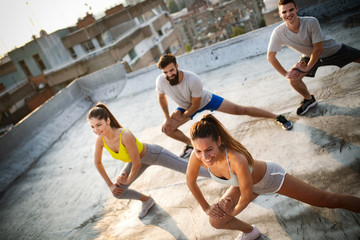 Group of happy fit friends exercising outdoor in city
