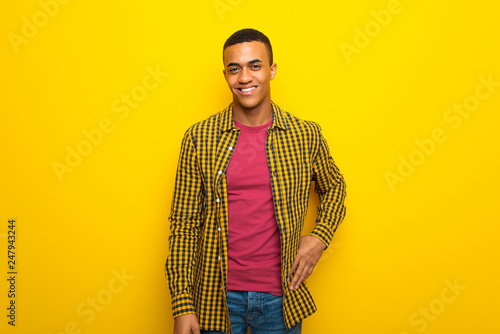 Foto Murales Young afro american man on yellow background posing with arms at hip and smiling