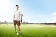 Handsome asian man in white clothes holding iron golf club walking on the golf course with sand bunkers, pond and trees