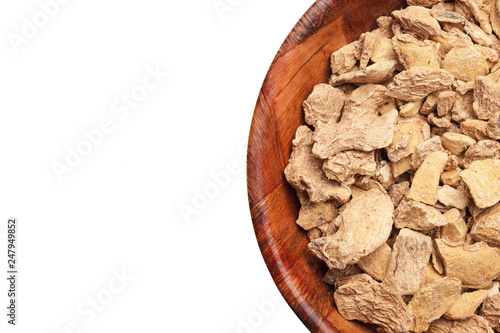 Ginger root pieces in wooden bowl. Kitchen spices container isolated on white studio background.