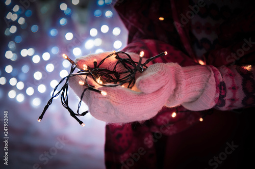 Lights, bokeh. Hands with electric mini lights. Garland in hands. Winter, garland in mittens. - 247952048