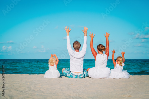 happy family with kids hands up on beach - 247960297