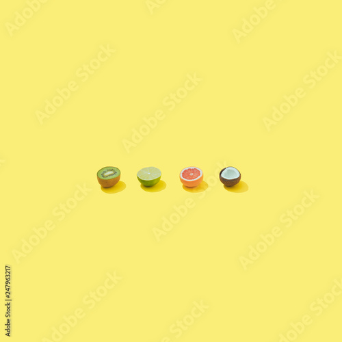 Tropical fruit on pastel yellow backround. Minimal summer food concept. - 247963217