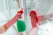 Partial view of woman in pink gloves cleaning window with spray and rag