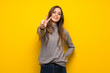 Leinwanddruck Bild - Young woman over yellow wall smiling and showing victory sign