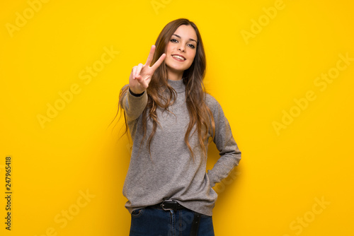Leinwanddruck Bild Young woman over yellow wall smiling and showing victory sign