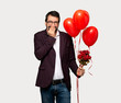 Man in valentine day smiling a lot while covering mouth over isolated grey background
