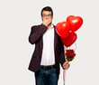 Man in valentine day covering mouth with hands for saying something inappropriate over isolated grey background