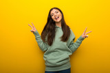 Teenager girl with green sweatshirt on yellow background smiling and showing victory sign with both hands - 247969601