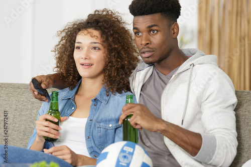 excited couple watching sports match on tv