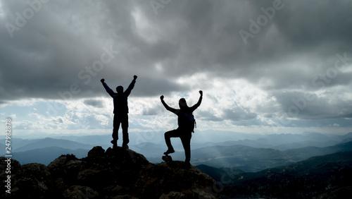 happy climbers reaching the goal and peak success