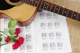 Acoustic guitar and table of chord. Learning to play the guitar