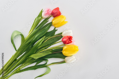 Leinwanddruck Bild top view of bouquet with colorful tulip flowers isolated on grey