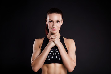 Strong woman bodybuilder with perfect abs, shoulders, biceps, triceps and chest. Photo of sporty young woman on black background. © Elena Kratovich