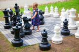 serious girl playing giant chess