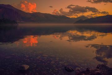 atardecer en un lago de aguas calma y con montañas al fondo
