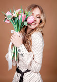 Fototapeta Tulipany - Happy beautiful woman with bouquet of spring tulips smilling over beige background. © svitlychnaja