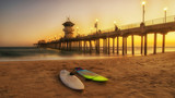 pier at sunset with surfboards in the sand