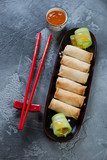Plate with chinese spring roll appetizers and chopsticks on a grey concrete background, vertical shot, flatlay - 248025401