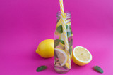 Detox water with lemon and mint in the glass bottle  on the pink  background