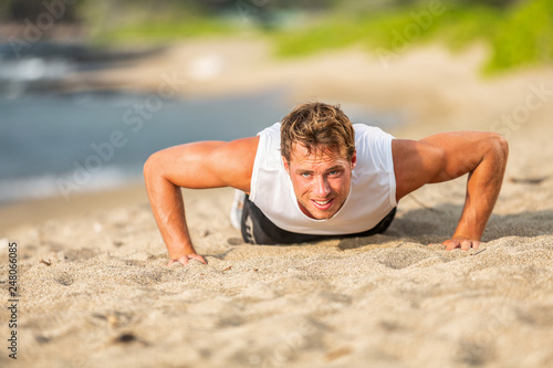 Leinwanddruck Bild Fit man athlete training hard doing push-ups on beach. Fitness motivation.