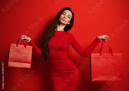 Woman in red tight dress holds two red shopping bags and holds lips like in a kiss - 248072471