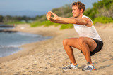Fitness workout fit man strength training doing squats on beach. Lower body legs exercises athlete.