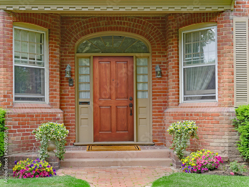 brick house with recessed entrance and elegant wooden front door - 248085083