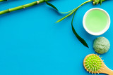 Asian spa treatment concept with natural ingredients. Spa salt, lotion, sponge near bamboo on blue background top view space for text