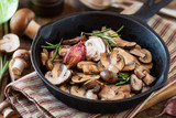 Cooked chestnut mushrooms or brown mushrooms in a cast iron skillet with rosemary and a clove of purple garlic