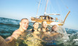Leinwanddruck Bild - Young millennial friends taking selfie and swimming at sailing boat sea trip - Rich guys and girls having fun in summer party day - Exclusive vacation concept - Bright sunny afternoon filter