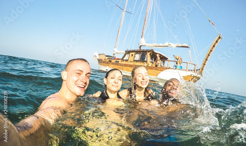 Leinwanddruck Bild Young millennial friends taking selfie and swimming at sailing boat sea trip - Rich guys and girls having fun in summer party day - Exclusive vacation concept - Bright sunny afternoon filter