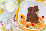 Fun Food for kids - Cute sweet Easter bunny shaped toast with chocolate spread and colourful sprinkles served with fresh fruit like kiwi, mandarines and apple for breakfast or lunch