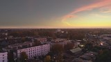 Aerial shot of a wintery sunset on top of a city with a distant big wheel - 248110204