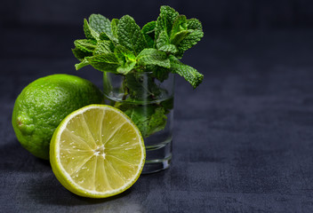 Fresh mint, lime and ice on a black background. Ingredient for mahito