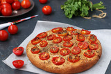 Focaccia with cherry tomatoes is located on parchment on a dark background. In the background is a bunch of parsley and a plate of tomatoes. Horizontal photo