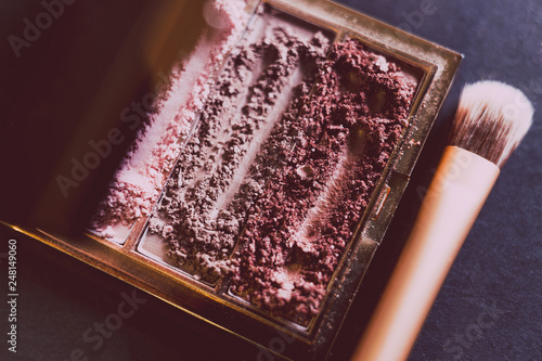 palette with crushed powder eyeshadows in nude and blush tones on dark background with brush © faithie