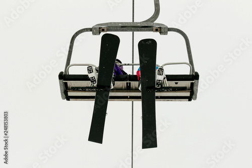 fototapeta na ścianę two snowboarders ride chairlift background in sky