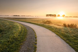 cycling road in countryside at misty sunrise - 248155429