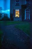 Illuminated window of house in twilight. - 248156499