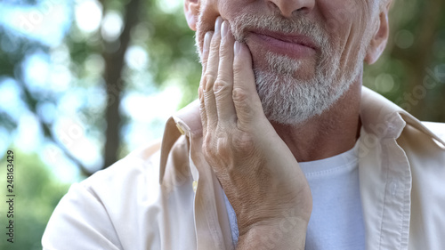 Leinwandbild Motiv Senior man having problem with teeth, social program of dental prosthetics