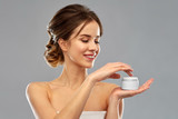 beauty, cosmetics and skincare concept - happy young woman holding jar of cream over grey background