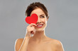 valentine's day, beauty and people concept - happy smiling beautiful young woman covering one eye by red heart over grey background