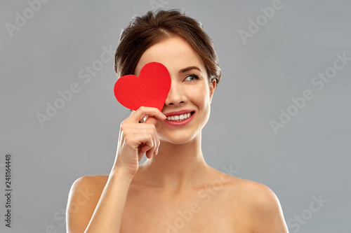 valentine's day, beauty and people concept - happy smiling beautiful young woman covering one eye by red heart over grey background - 248164448