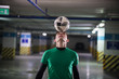 Football concept. Soccer player holding a ball on his head. Parking lot